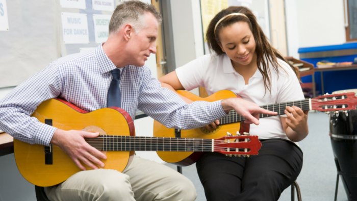 Photo of guitar teacher and student